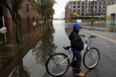 A child stands astride his bicycle on flooded street in the Red Hook section of Brooklyn after Hurricane Sandy caused extensive damage in the area on...