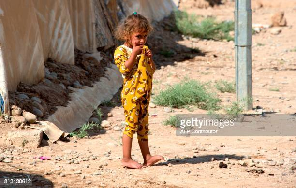 A child stands at a UNHCR refugee camp in Hammam alAlil on the outskirts of Mosul on July 12 2017 Iraqi Prime Minister Haidar AlAbadi announced in...