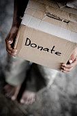 A child stands, barefoot, holding a box labeled donate