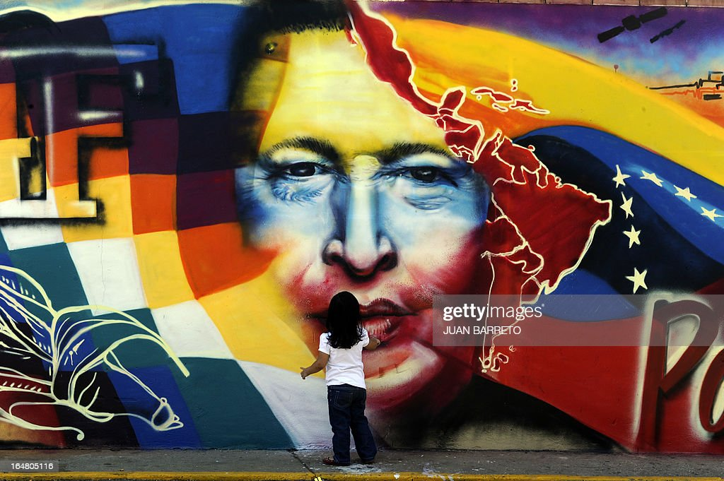 A child stands in front of a graffitti at the Mountain Barracks (Cuartel de la Montana) where the remains of late Venezuelan President Hugo Chavez are staying in, in the 23 de Enero low income neighborhood in Caracas, on March 28, 2013.