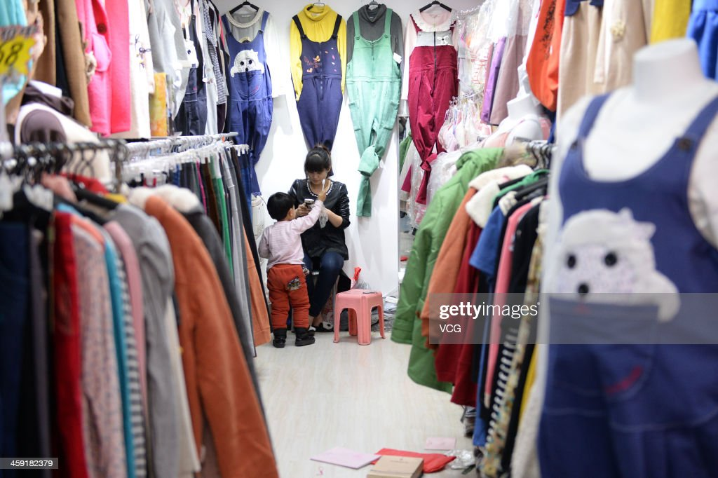 A child stands in front of a woman while she plays mobile phone in the Zoo clothing market on December 23, 2013 in Beijing, China. The Zoo clothing market is a massive wholesale market actually comprises seven markets. This incredible indoor market, and the similarly laid out buildings around it, have mazes of shops and stalls with wonderfully inexpensive clothes, shoes, and accessories. A large garment wholesale market in Beijing is expected to move to Hebei province in 2014 to help ease heavy traffic in the Chinese capital.