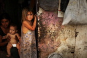 A child stands in the shack she shares with her family beside a dumpster in a gang infested neighborhood on July 17 2012 in Tegucigalpa Honduras The...