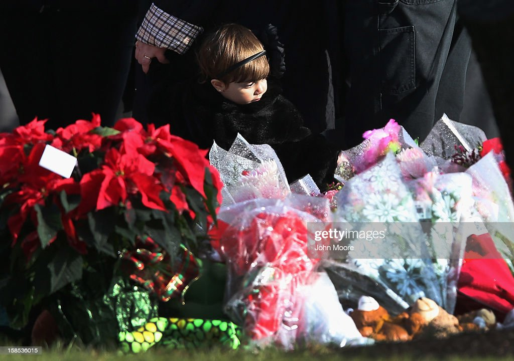 A child stands next to a makeshift memorial for Jessica Rekos, 6, following her funeral at the St. Rose of Lima Catholic church on December 18, 2012 in Newtown, Connecticut. Funeral services were held at the church for both Jessica Rekos and James Mattioli, 6, Tuesday, four days after 20 children and six adults were killed at Sandy Hook Elementary School.
