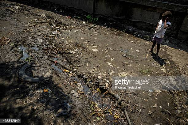 A child stands on a drainage ditch in a slum in the city of Beira on September 28 2015 in Beira Mozambique