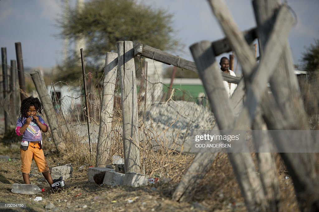 A child stands on a lot on July 9, 2013 in the Nkaneng shantytown next to the platinum mine, run by British company Lonmin, in Marikana. On August 16, 2012, police at the Marikana mine open fire on striking workers, killing 34 and injuring 78, during a strike was for better wages and living conditions. Miners still live in dire conditions despite a small wage increase.