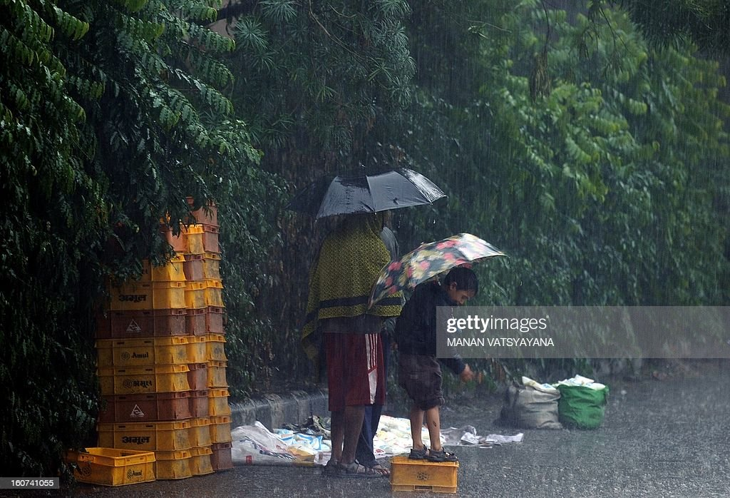A child stands on an overturned milk basket during a heavy downpour in New Delhi on February 5, 2013. Heavy rains lashed the Indian capital bringing down the mercury and throwing normal life out of gear.