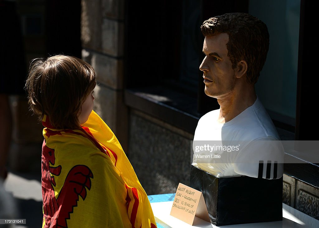 A child stares at a cake replica of <a gi-track='captionPersonalityLinkClicked' href=/galleries/search?phrase=Andy+Murray+-+Tennis+Player&family=editorial&specificpeople=200668 ng-click='$event.stopPropagation()'>Andy Murray</a> after winning Wimbledon pictured in Dunblane on July 8, 2013 in Dunblane, Scotland.