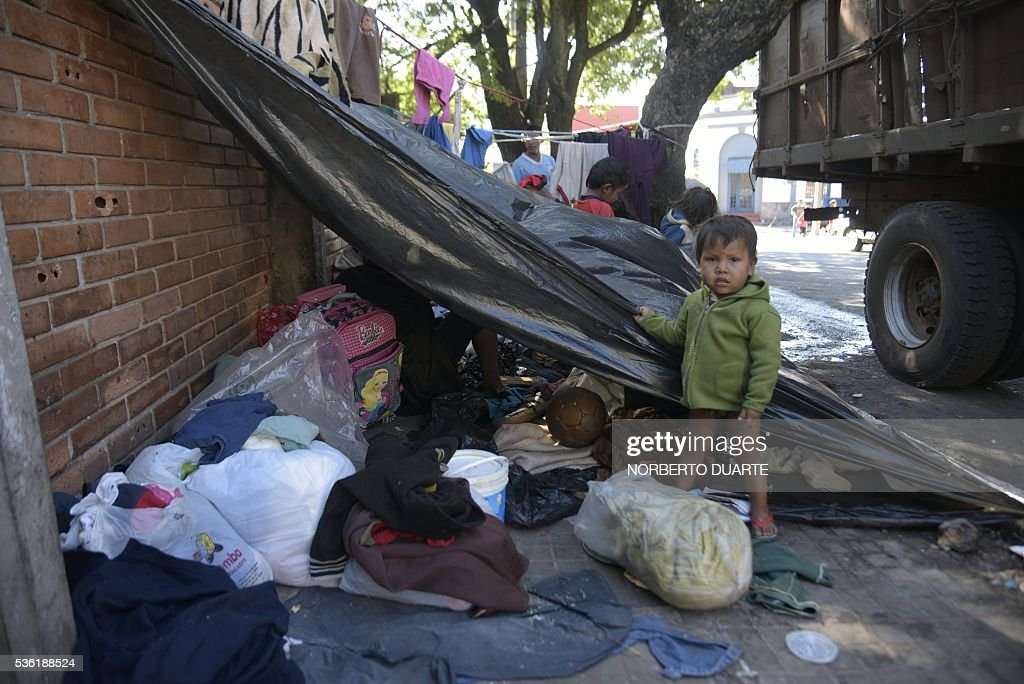A child stays in an encampment of natives of the Mbya ethnic group set in front of the Paraguayan Institute for the Natives (INDI) in Asuncion on May 31, 2016. The Mba are camped since 30 days ago demanding to the government to be granted the ownership of the 500 hectares of land they live in. / AFP / NORBERTO