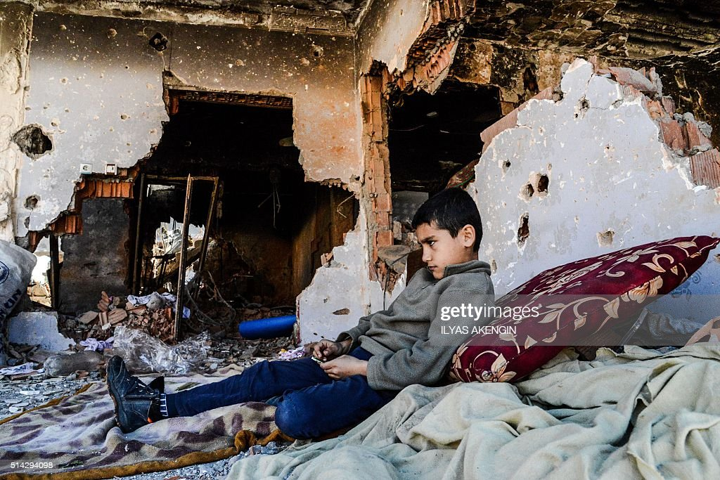 TOPSHOT A child stays next to his ruined house on March 8 2016 in Cizre district Residents of Cizre in southeastern Turkey began returning home...