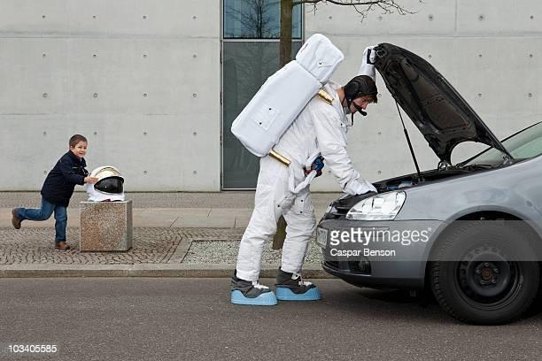 A child stealing a space helmet while an astronaut repairs his broken car