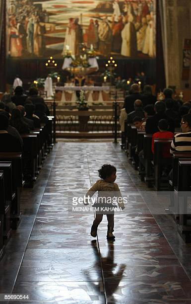 A child strolls down the aisle as Israeli Arab Christians attend Sunday mass at the Church of the Annunciation believed to stand at the site of...