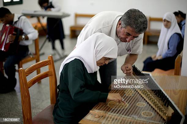 A child suffering from the Down syndrome plaus the qanun during a music class at a specialised school of the 'Right to Live Society' a Palestinian...