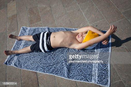 Child sunbathes with deflated beachball on head : ストックフォト