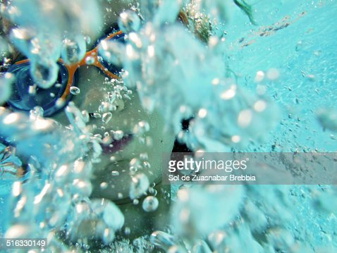 Child surrounded by bubbles under water : Stock Photo