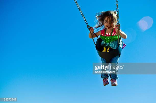 Child swinging high in sky