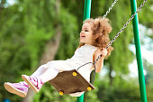 Child swinging on a swing at  playground in the park. Children Protection Day.