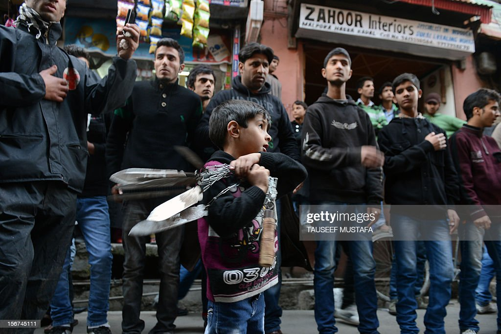 A child swings blades as other Kashmiri Shiite Muslims perform a ritual of self-flagellation with knives during a religious procession held on the fourth day of Ashura, which remembers the slaying of the Prophet Mohammed's grandson in southern Iraq in the seventh century, in Srinagar on November 20,2012. During the Shiite Muslim holy month of Muharram, large processions are formed and the devotees parade the streets holding banners and carrying models of the mausoleum of Hazrat Imam Hussain and his people, who fell at Karbala. Shias show their grief and sorrow by inflicting wounds on their own bodies with sharp metal tied to chain to depict the sufferings of the martyrs. AFP PHOTO/ Tauseef MUSTAFA