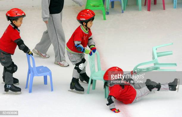 A child takes a fall as young skaters use chairs as guides during iceskating class at a Beijing shopping mall 30 March 2005 China's economic reforms...
