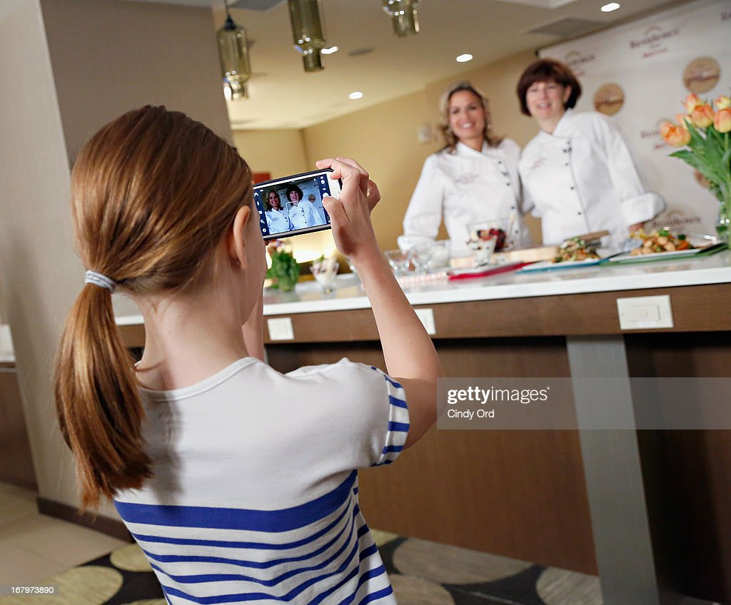 A child takes a photo of award recipient, chef and lifestyle entrepreneur <a gi-track='captionPersonalityLinkClicked' href=/galleries/search?phrase=Cat+Cora&family=editorial&specificpeople=4166787 ng-click='$event.stopPropagation()'>Cat Cora</a> and Residence Inn by Marriott VP and Global Brand Manager, Diane Mayer at the 2013 Resident Mom of the Year event at Residence Inn by Marriott on May 3, 2013 in New York City.