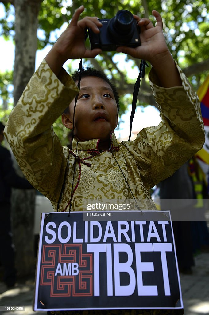 A child takes a picture during a demonstration outside the Chinese consulate in Barcelona on May 17, 2013 in Barcelona, to demand human rights freedom in Tibet and dialogue between the Dalai Lama and Beijing.