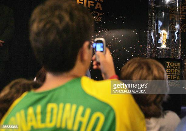 A child takes a picture with his celphone of the FIFA soccer World Cup trophy which will be disputed during the FIFA Germany 2006 World Cup 20...