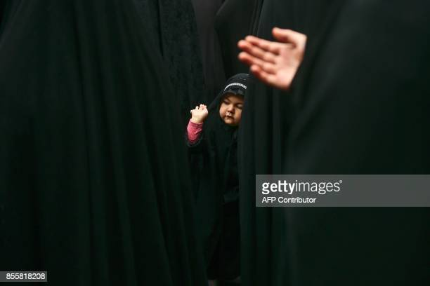 A child takes part with Turkish Shiite women in a religious procession held for the Shiite religious holiday of Ashura on September 30 in Istanbul...