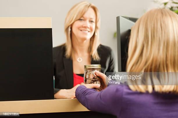Niño de tomar su moneda pote de ahorro a cajero de banco