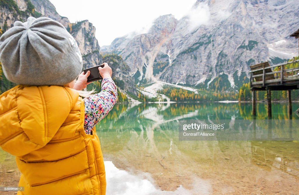 Child taking photo of lake braies, italy. rear view : Stock Photo