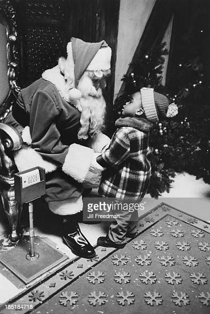A child talks to a man dressed as Santa Claus in Macy's department store New York City 1973