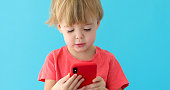 Concentrated child tapping cell phone screen, interest in modern technology. Pretty boy blue background