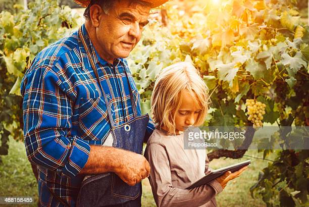 Child teaches to a farmer man using tablet pc