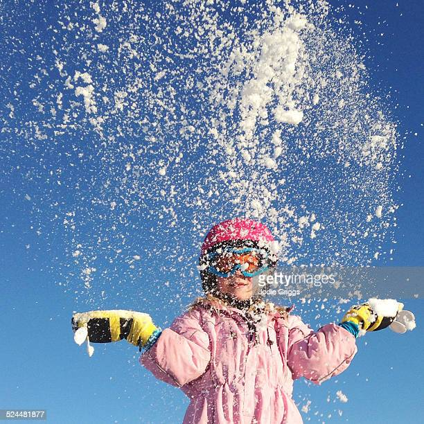 Child throwing a handful of snow up into the air