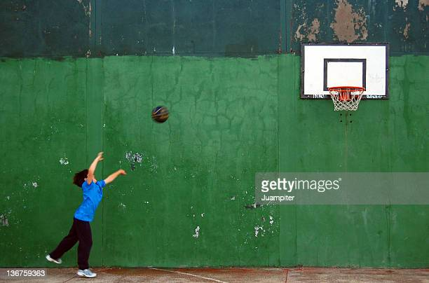 Child throwing ball to basketball