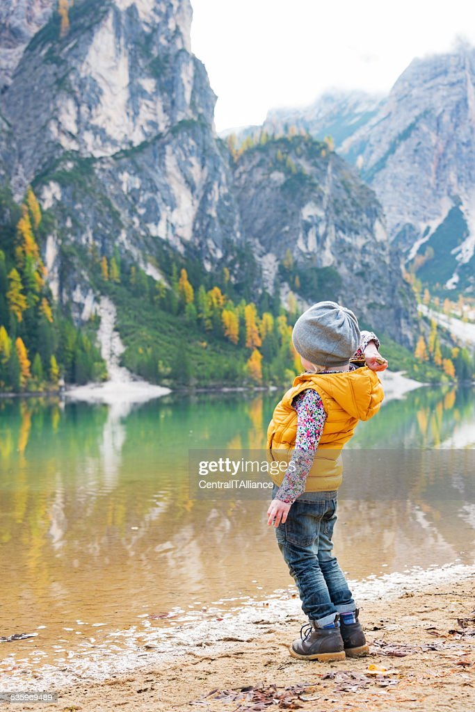 Child throwing stones while on lake braies, italy : Stock Photo