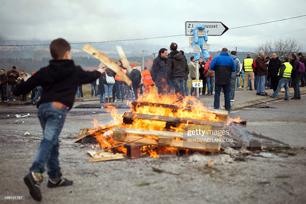 A child throws wood into a fire as workers of semiconductor manufacturer LFoundry block the access to the Industrial Zone in Rousset, near Aix-en-Provence, southern France, on December 23, 2013, after trade unions announced that a court had ordered a judicial liquidation of their factory. Over 670 jobs are at risk if the factory closes and approximately 400 workers took part in the protest and blocade of the Rousset industrial zone, as French Minister for Industrial Renewal Arnaud Montebourg prepared to receive a delegation of workers in Paris today.