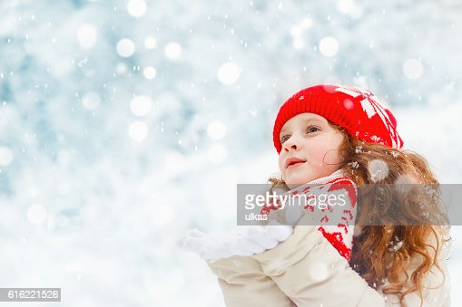Child to catch falling snowflakes. : Stock Photo