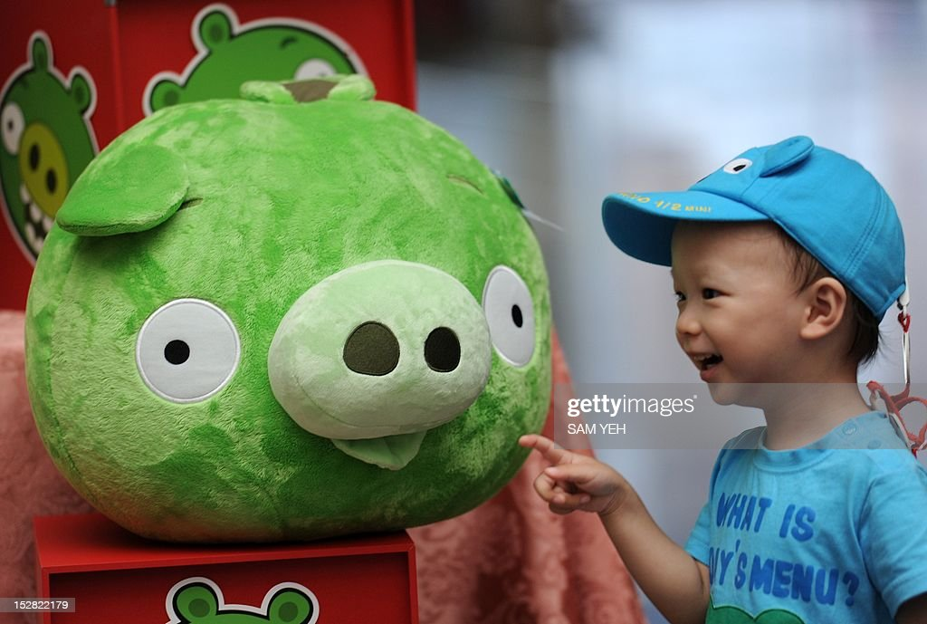 A child touches a Bad Piggies stuffed toy from the Angry Birds game during a press conference in Taipei on September 27, 2012. 'Angry Birds' maker Rovio is to launch a new title allowing users to play as the 'Bad Piggies' from the smash-hit game, and take revenge on the birds who attacked them with slingshots. AFP PHOTO / Sam Yeh