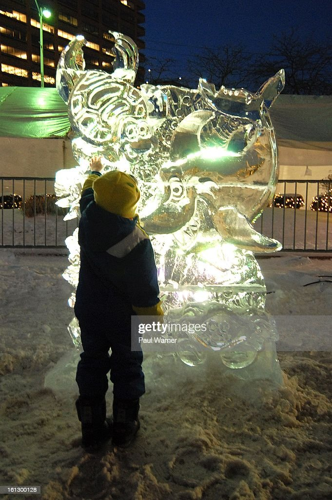 A child touches a ice sculpture at Motown Winter Blast at Campus Martius Park on February 9, 2013 in Detroit, Michigan.
