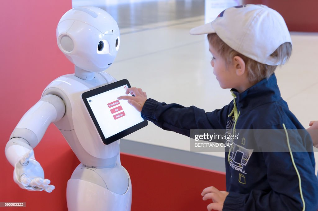 A child touches the screen of Pepper the robot to get informations at the Cite des Sciences et de l'Industrie museum in Paris on June 13, 2017. /