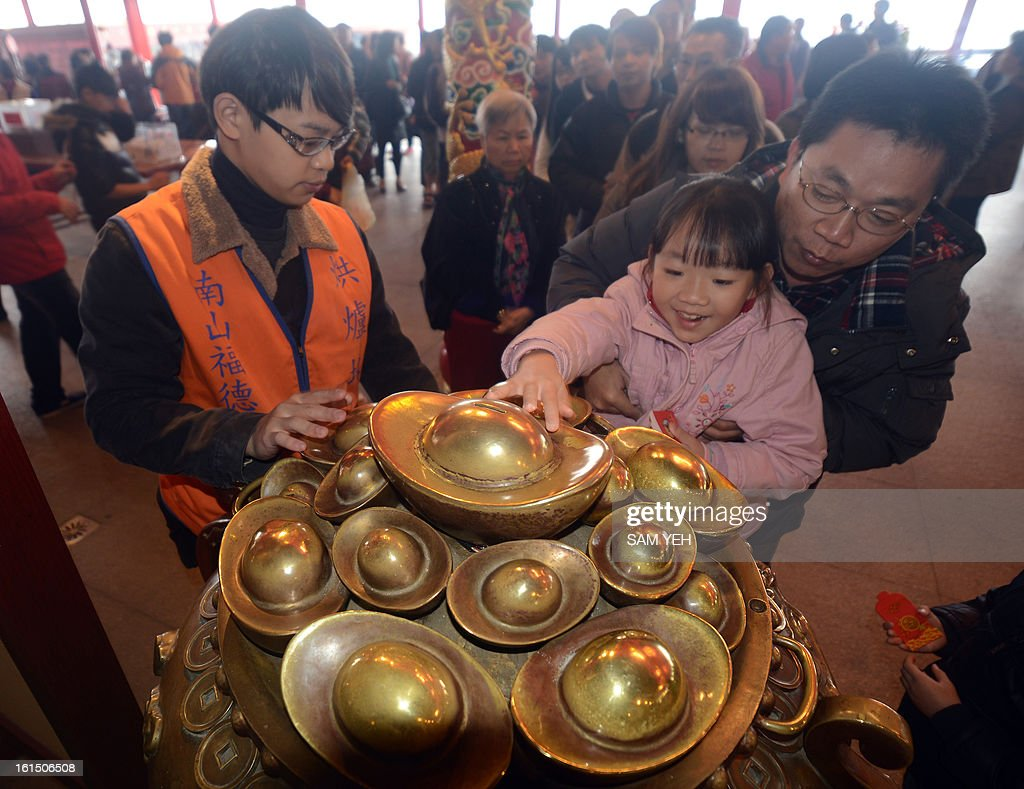 A child touches the Yuan Bao (money) for good fortune at Hongludi temple, a Taoist god of fortune, in Chunghe, the New Taipei City, on the third day of the lunar new year on February 12, 2013. Chinese lunar new year, celebrated by Chinese communities the world over, falls on February 10 with the beginning of the new moon. AFP PHOTO / Sam Yeh