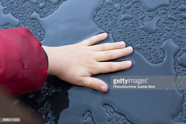 Child touching wet metallic surface
