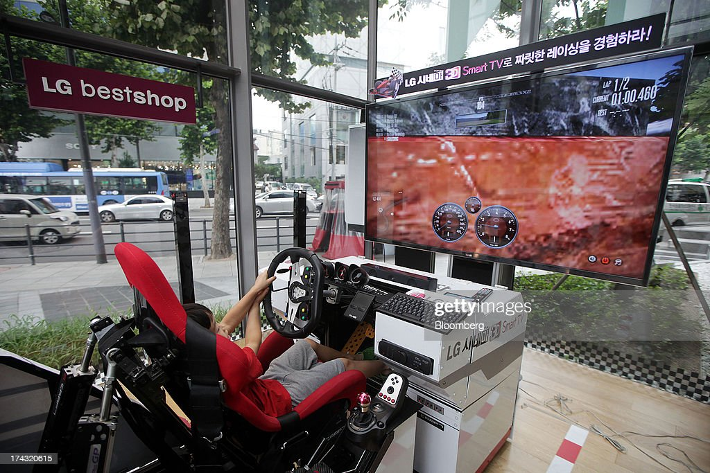 A child tries out a video game at an LG ELectronics Inc. bestshop store in the Gangnam area of Seoul, South Korea, on Wednesday, July 24, 2013. LG Electronics, the worlds second-largest television maker, posted second-quarter profit that missed analyst estimates on slowing demand for sets and increased spending on marketing for smartphones. Photographer: Woohae Cho/Bloomberg via Getty Images