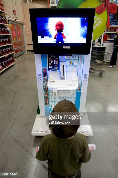 A child tries out a Wii game at the WalMart store November 20 2007 in Secaucus New Jersey The holiday shopping season 'officially' starts Friday...