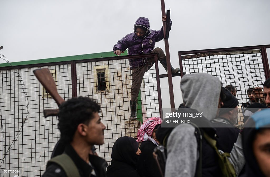 A child tries to climb over a fence as Syrians fleeing the northern embattled city of Aleppo wait on February 6, 2016 in Bab-Al Salam, near the city of Azaz, northern Syria, near the Turkish border crossing. Thousands of Syrians were braving cold and rain at the Turkish border Saturday after fleeing a Russian-backed regime offensive on Aleppo that threatens a fresh humanitarian disaster in the country's second city. Around 40,000 civilians have fled their homes over the regime offensive, according to the Syrian Observatory for Human Rights monitor. / AFP / BULENT KILIC