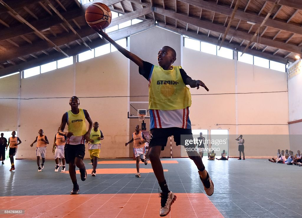 Child tries to shot the ball during a basketball match of the four days of workshop with the American player Tommy Davis organised by the US embassy at the Felix Houphouet-Boigny University in Abidjan on May 25, 2016. / AFP / ISSOUF