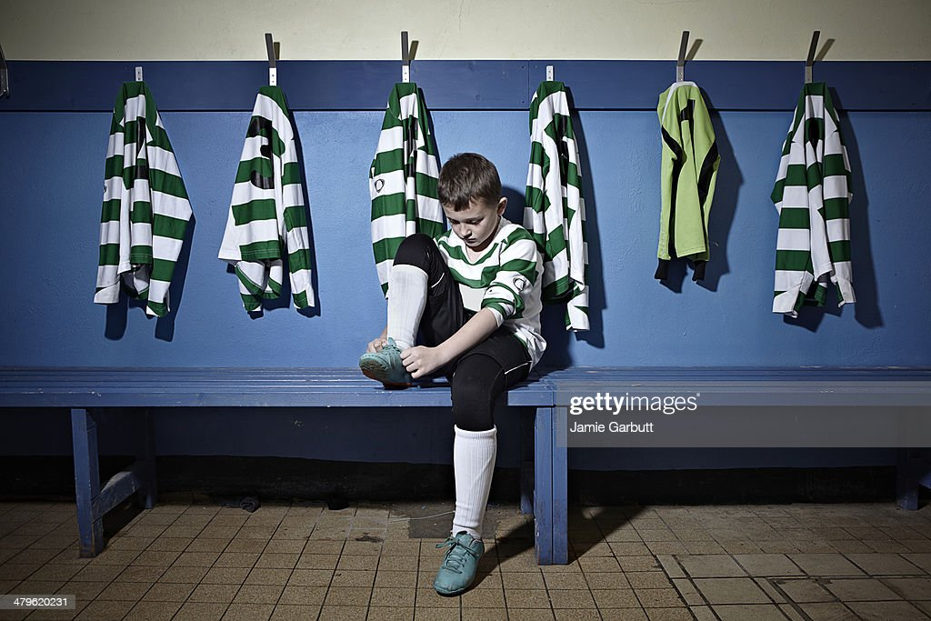 A child tying his shoelaces before a match : Stock Photo