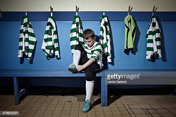 A child tying his shoelaces before a match
