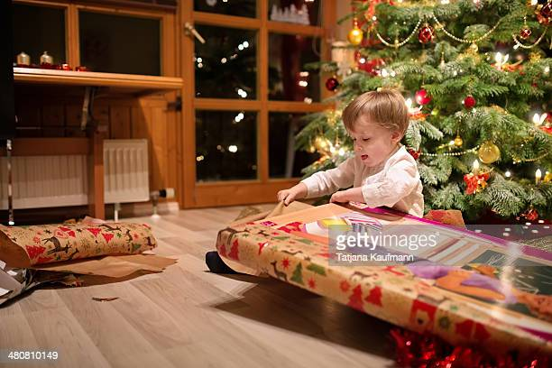 Child unwrapping Christmas Gift in front of Tree