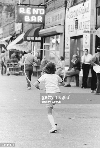 A child uses a hulahoop like a jump rope as grown men lean against a wall near the Reno Bar Second Avenue Lower East Side New York 1967