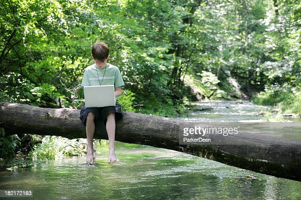 Child Uses Computer in Nature, Sitting on Log Over River